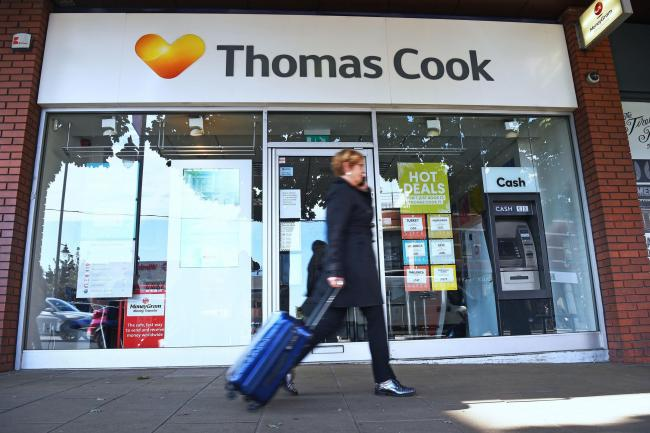 PA file photo of a woman walking past a Thomas Cook high street store.See PA Feature TOPICAL Travel Package. Picture credit should read: Kirsty O'Connor/PA. WARNING: This picture must only be used to accompany PA Feature TOPICAL Travel Package.