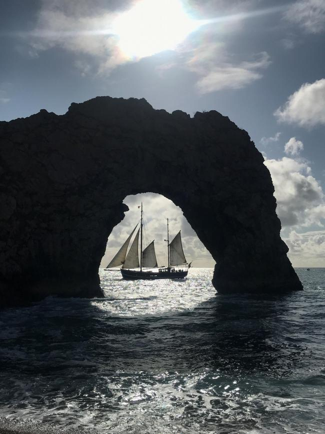 Sailing boat as seen through Durdle Door arch by Kayla Smith