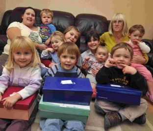 Katie and Karen Elliott and children at Dolls House childminders in Chickerell with some of their Treats for Troops boxes