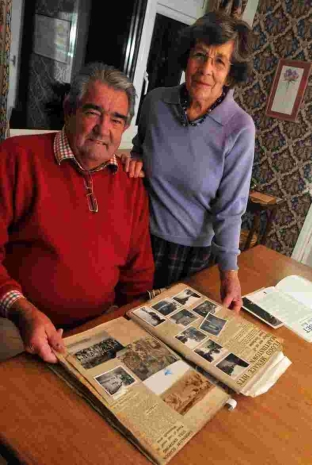 Richard King looks at his mother's scrapbook on the floods at Martinstown in 1955 with historian Margaret Hearing