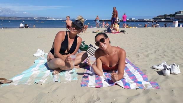 Dorset Echo: Dancers Crystal and Jodie soak up the rays on Weymouth Beach Picture: Ellie Maslin