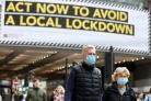 People wearing face masks walk past a local lockdown sign