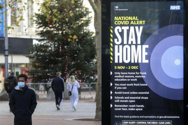 People walk past a Covid alert poster