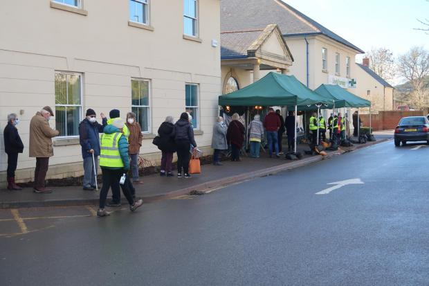 Dorset Echo: People line up outside the Bridport Medical Center to receive their first coronavirus jab.