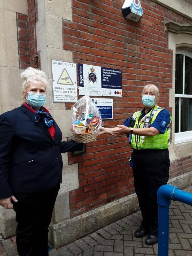 Dorset Echo: Castle View escort team leader Katja Williams, left, hands Dorchester Police Station a gift basket to Community Safety Officer Sarah Pilcher Photo: Deep South Media