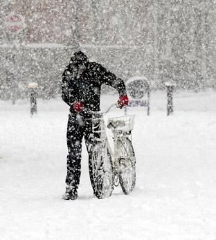 A man pushes a bicycle through a blizzard in York