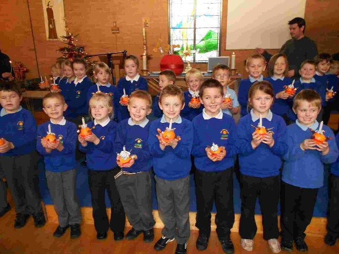 GOOD CHEER: Year two pupils from Bincombe Valley Primary School with their Christingles at St Francis Church