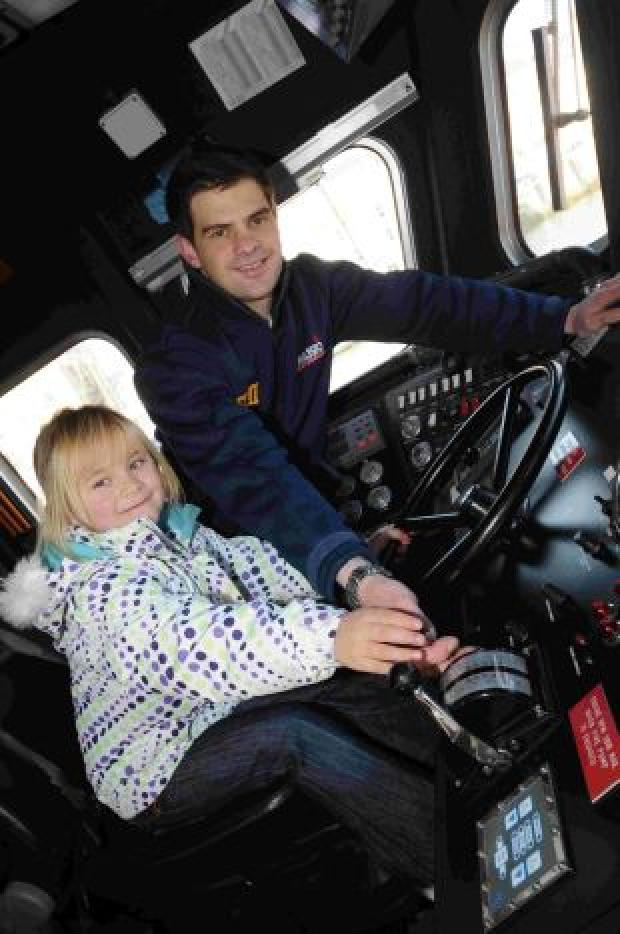 IN CONTROL: Crew member Paul Charloner with six-year-old Olivia Hallet at the helm