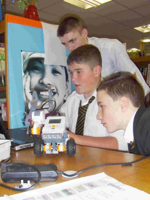 Dorset Echo: ROBOT WARS: Jack Record explaining the finer points of his design to Aiden Goalby and Aden Milnes. Inset right, Dylan Tuffin tests his solution