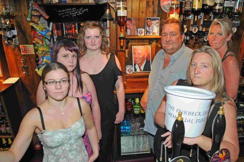 GIVE GENEROUSLY: Jo Evans, Emma Brooks, Jenna Wells, Pete and Tracey Whittle and Laura Conn with one of the collection buckets at the King's Arms in Weymouth
