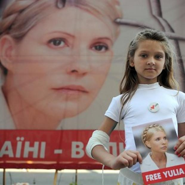 A young girl stands in front of a banner supporting imprisoned opposition leader Yulia Tymoshenko in Kiev, Ukraine