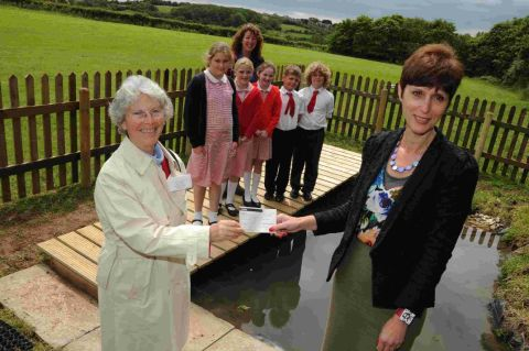 NEW POND: Dorset Gardens Trust's Rosemary Agg, left, presents a cheque to Radipole Primary School headteacher Veronique Singer, watched by Field to Fence's Michelle Eastlake and Year Five pupils