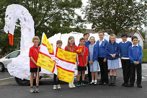 Torch bearers from Radipole hand over to Southill Primary, in front of the swan car