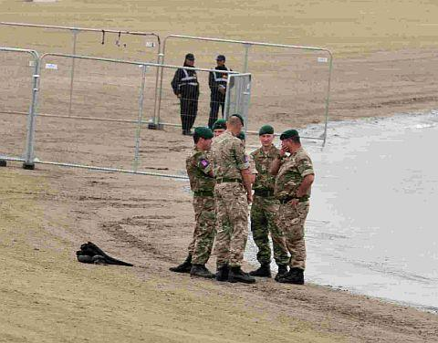 A member of the armed forces and a party of Royal Marines carrying out a security sweep prior to the Olympic Torch music concert on the beach