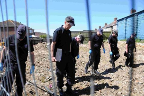 Forensic officers and armed police look for vital evidence
