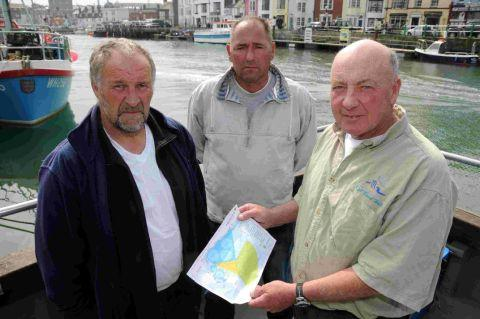 Dorset Echo: STOPPED FROM WORKING: Andy Alcock, Hugh Cox and David Pitman with a map showing the restricted areas of the sea