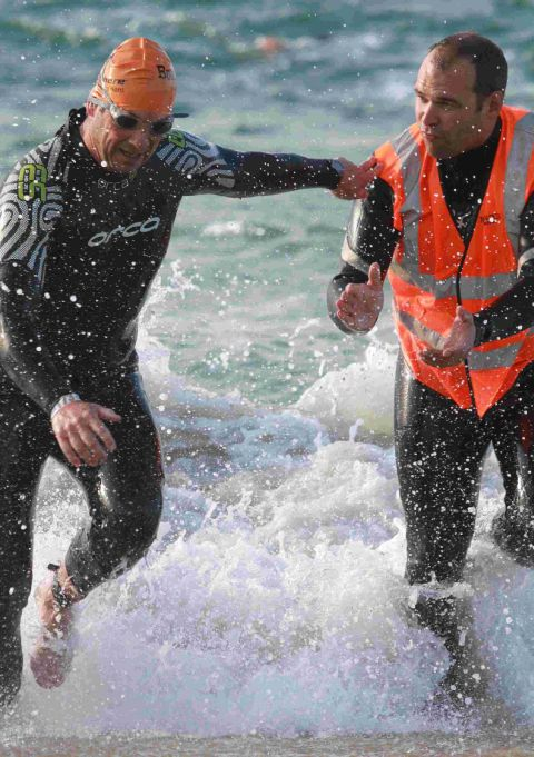 KEEP GOING: Triathlete Nick Wall is encouraged by BustinSkin race marshal Mike Kerslake at a previous event