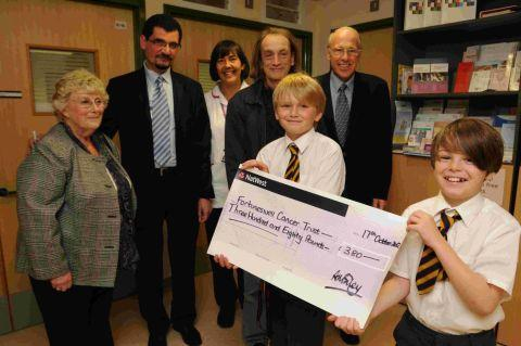 Dorset Echo: ON OUR BIKES: James Biley and William Hough present their fundraising cheque to the Fortuneswell Unit at Dorset County Hospital