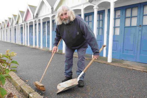 CLEANING UP: Derek Walker sweeps up the broken glass at the Greenhill chalets