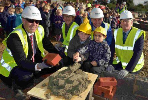 BUILDING SIGHT:  Paul Gale of Morgan Sindall, former headteacher Viv Burgess, headteacher Dan Hunwick and county council project manager Fred Wellstead with pupils Jack and Bailey