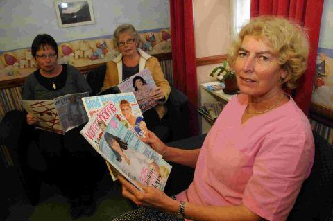 CURTAINS FOR MAGS: Lyme Regis dentist Monica Symes and patients Maggie Pratt and Pauline Brownjohn in the waiting room currently enjoy reading their magazines