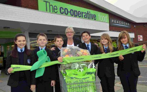 Cutting the ribbon: Co-op store manager Jan Dyer with pupils at the opening