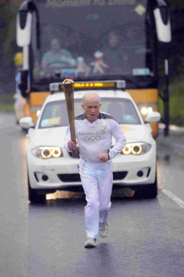 PROUD MOMENT: Peter Fry carries the Olympic torch in Weymouth