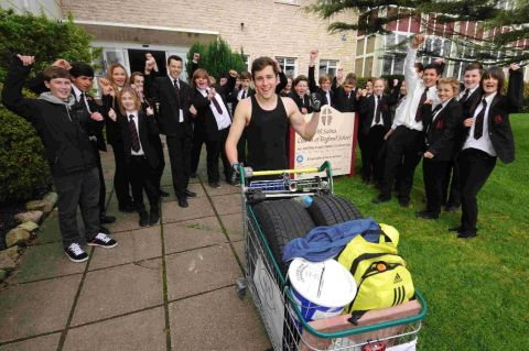 WELL DONE: All Saint's School pupil Lewis Taylor with year 10 pupils cheering his arrival at the school after his long push