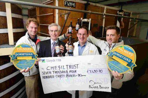 CHEQUE: Team GB sailors Ben Rhodes and Stevie Morrison and chairman of the trustees of the Chesil Trust David Dunn receive a cheque from Palmers head brewer Darren Batten