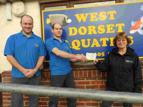 THANKS: Alayne Barron from the Echo's promotions team receives a £100 cheque for the Christmas Toy Appeal from Howard Cogan, far left, and Andrew Givens from West Dorset Aquatics