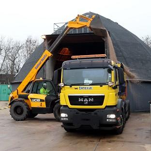 A Highways Agency worker loads gritting salt as snow hits parts of the country
