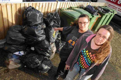 WHAT A LOAD OF RUBBISH: Kathleen Kelly and Franchesca Hills with the bagged piles of rubbish on Holland Road, Weymouth	HG10438/HG10437