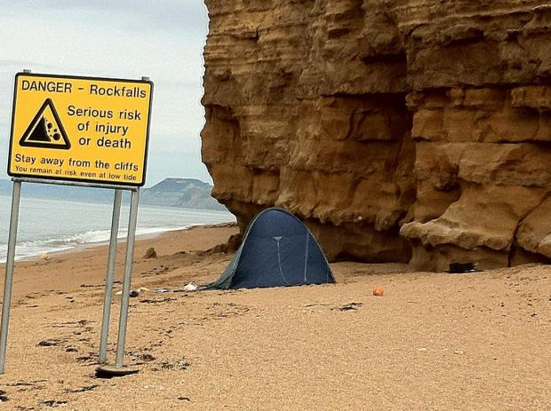 Campers pitch tent at foot of unstable cliff