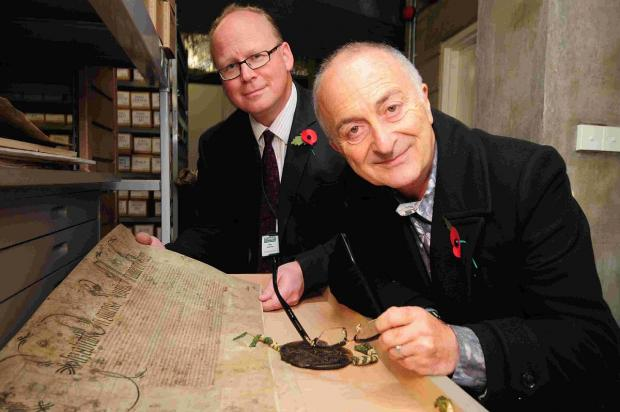 Dorset Echo: ANCESTORS: Tony Robinson in the archive room at Dorset History Centre with Sam Johnston looking at one of the Royal Charters from 1557