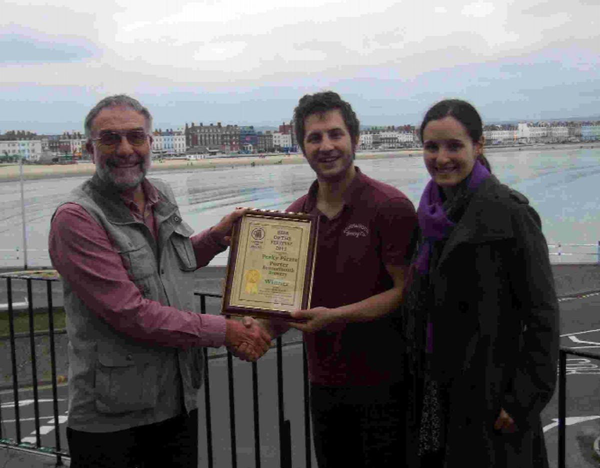 CHEERS!: Dave Harris, left, presents the Beer of the Festival certificate to Chris Mathers and Dr Hannah Farnfield