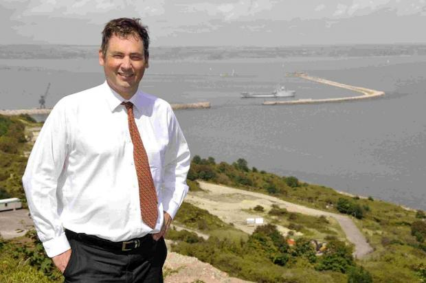 Dorset Echo: WELL PLAN: Andrew Hindle, chief executive of InfraStrata with a view of the drilling site behind him