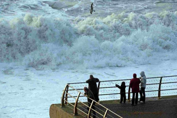Dorset Echo: Onlookers watch the stormy seas at Chesil Beach, Portland