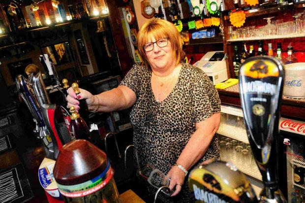 TIME PLEASE: Sally Dunn behind the bar of the Albert Inn