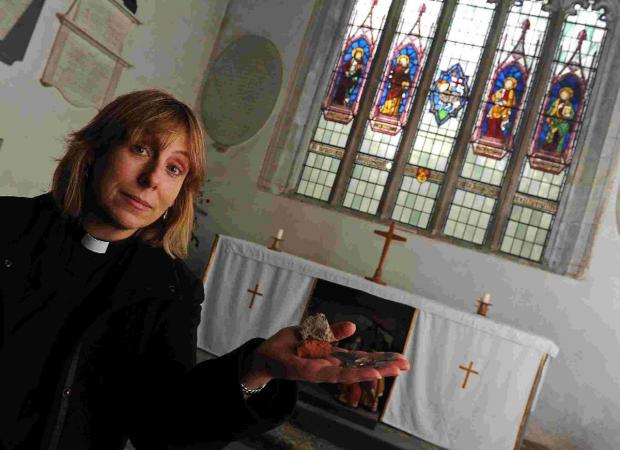 Rev Deb Smith with the stones that were thrown through the window  Picture: FINNBARR WEBSTER