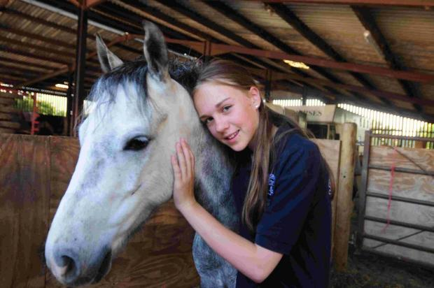 Dorset Echo: SAFE AND SOUND: Lexie Macduff, 11, with Boozie the horse following its rescue from a gate by a Bere Regis fire crew