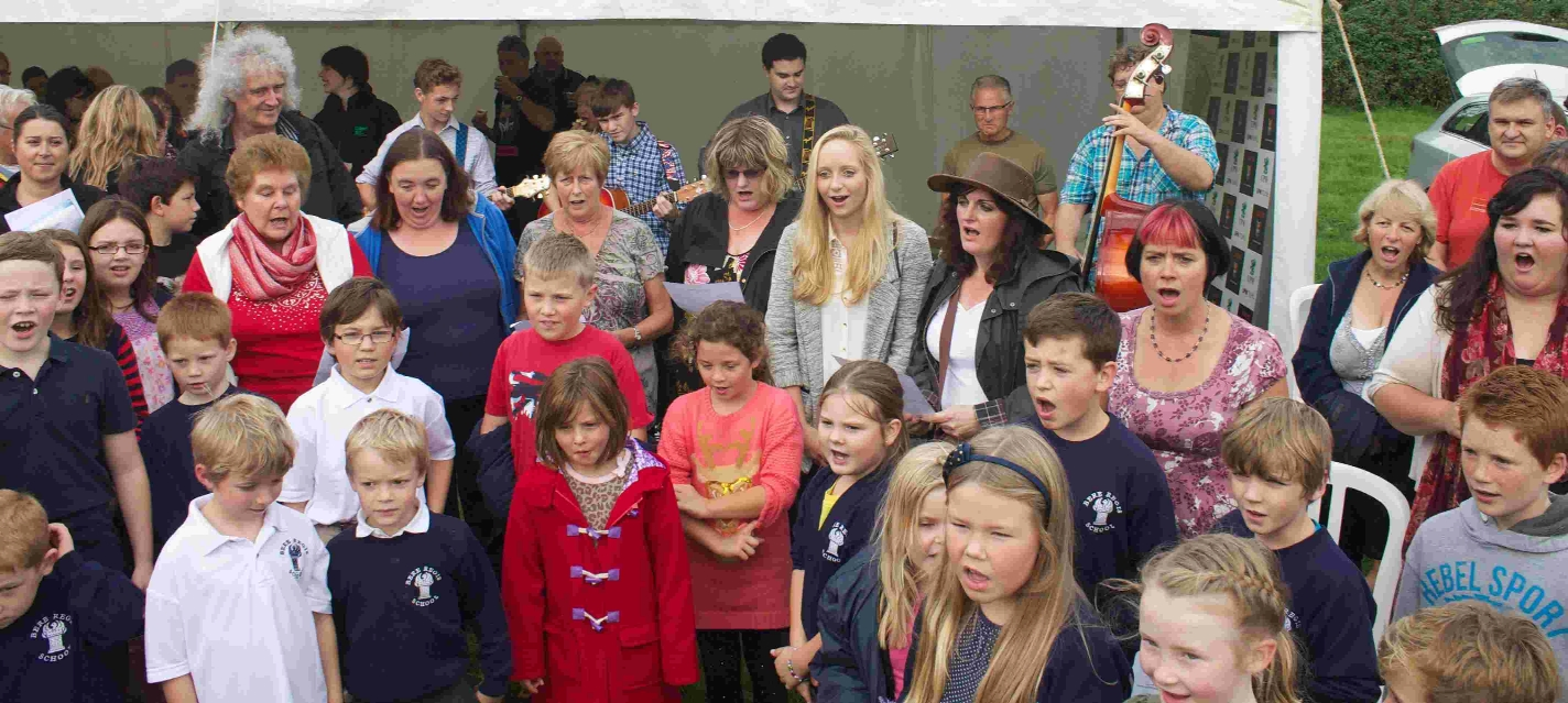 Brian May watching the schoolchildren sing the New Woodland Song, last year