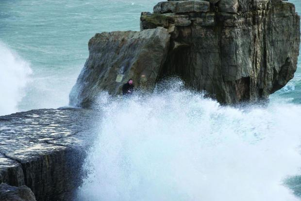 PERIL: A man and child get a close-up of waves crashing against Pulpit Rock at Portland Bill