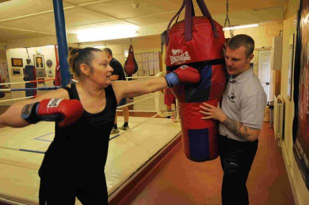 Lewis Chambers holds the punchbag for fellow support worker Tracy Walker