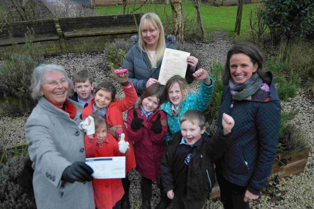 Rosemary Agg, left, from Dorset Garden Trust hands pupils at Piddle Valley First School a cheque
