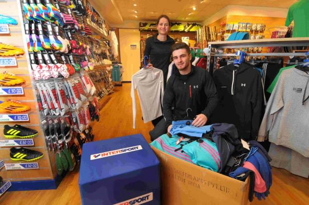 CELEBRATING: Staff at Intersport Tony Pryce, Colette Martin and Sam Coombes putting stock out ready for the opening