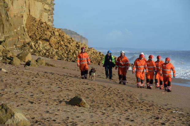 Dorset Echo: OPERATION: Rescuers with the sniffer dog  Picture: JOHN GURD