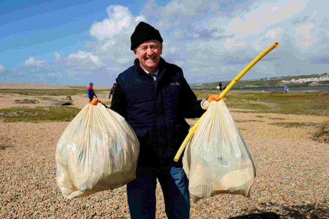 Volunteer Geoff Serle with bags of rubbish he collected