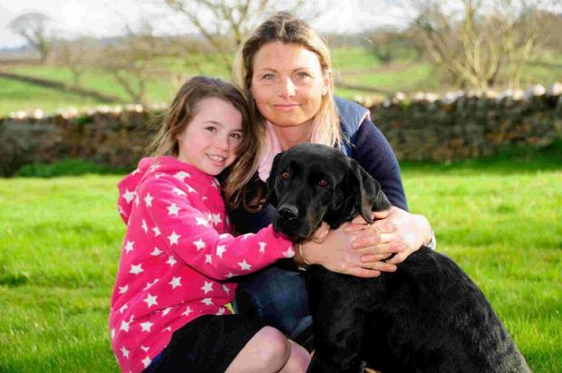 Dorset Echo: CRISIS: Mimi and Nikki Jones with their black labrador Minnie. Right, an X-ray reveals the hook