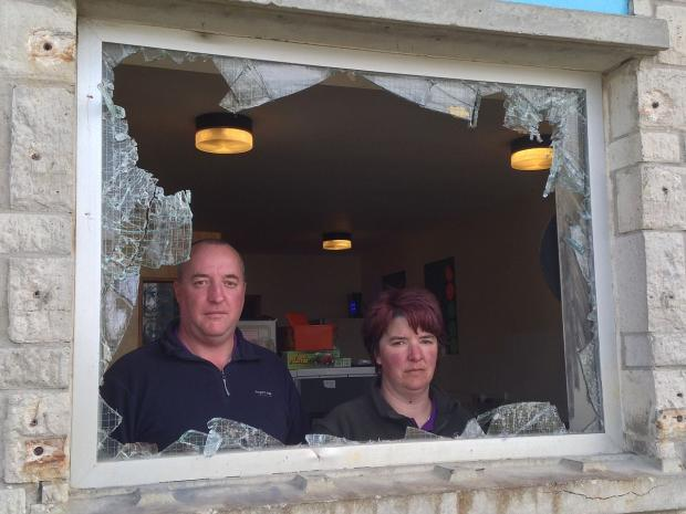 Jon and Su Illsley standing behind the broken window