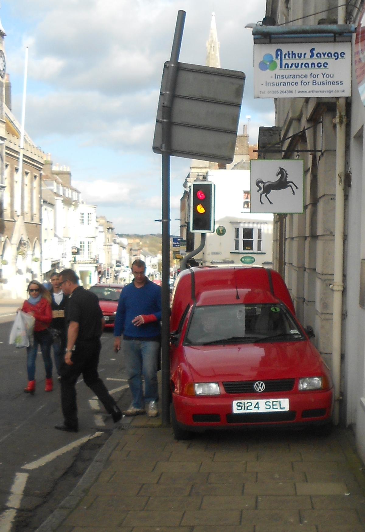 Car gets stuck between building and signpost in Dorchester